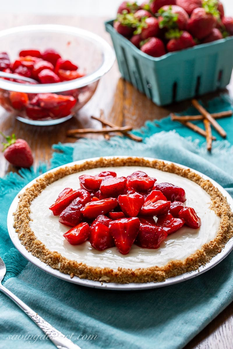 A cream cheese pie with pretzel crust topped with sliced strawberries