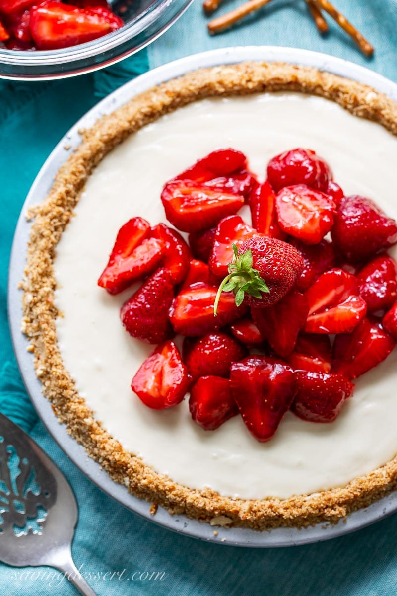 An overhead view of a cream cheese pie topped with fresh strawberries