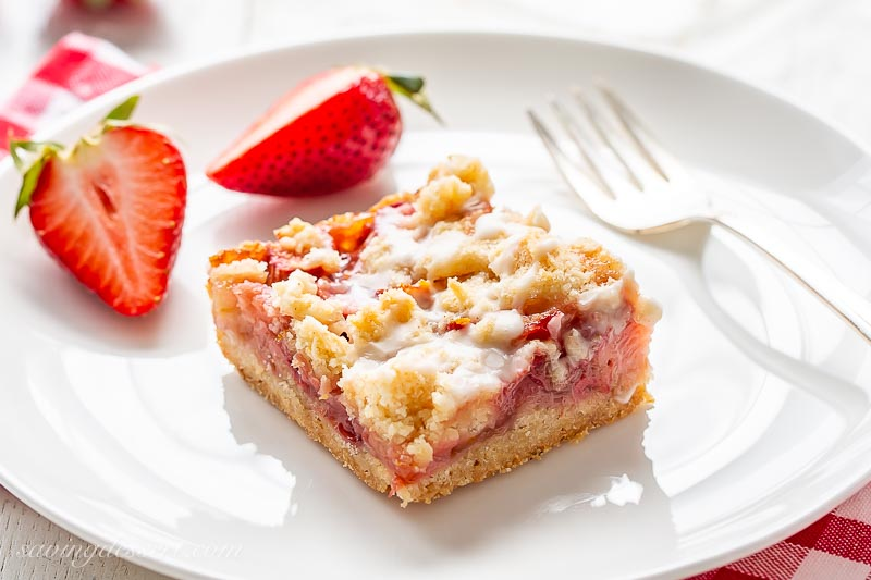A square fruit bar with a crumble top served with sliced strawberries