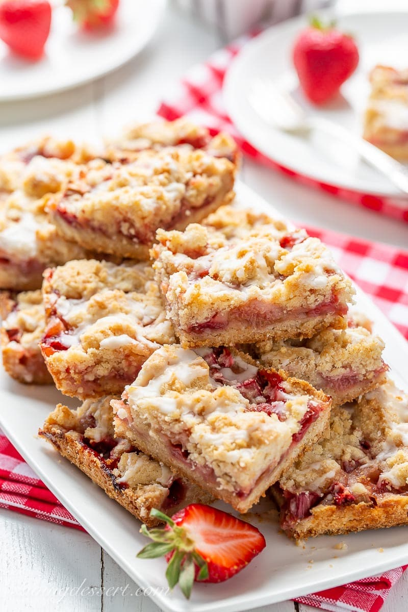 Crumble fruit bars stacked on a platter with strawberries