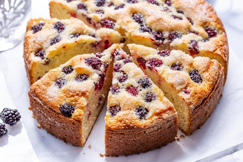 A sliced single layer blackberry cake with a crunchy sugary top