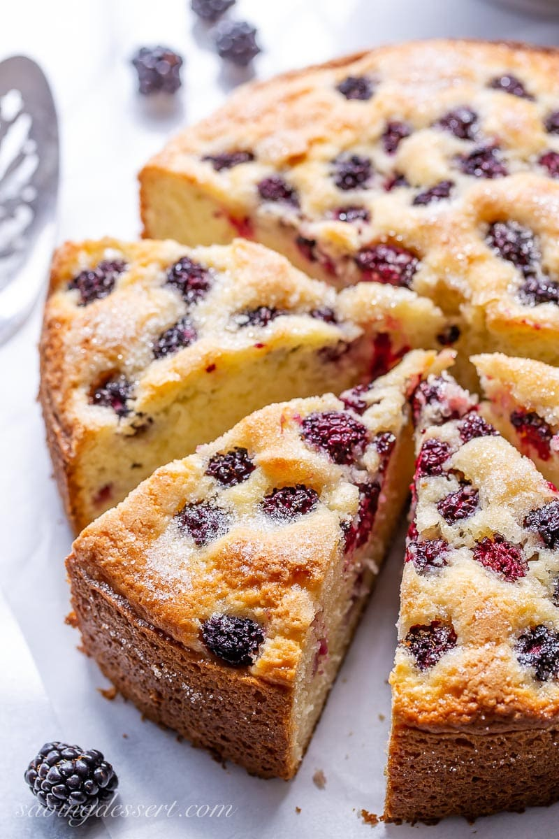 A sliced blackberry cake with a sugary top