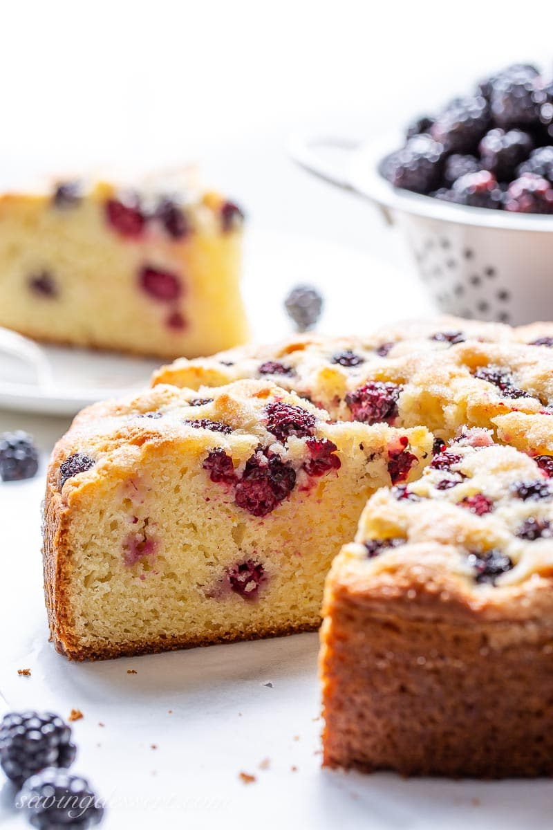A side view of a sliced cake with fresh blackberries and more in the background