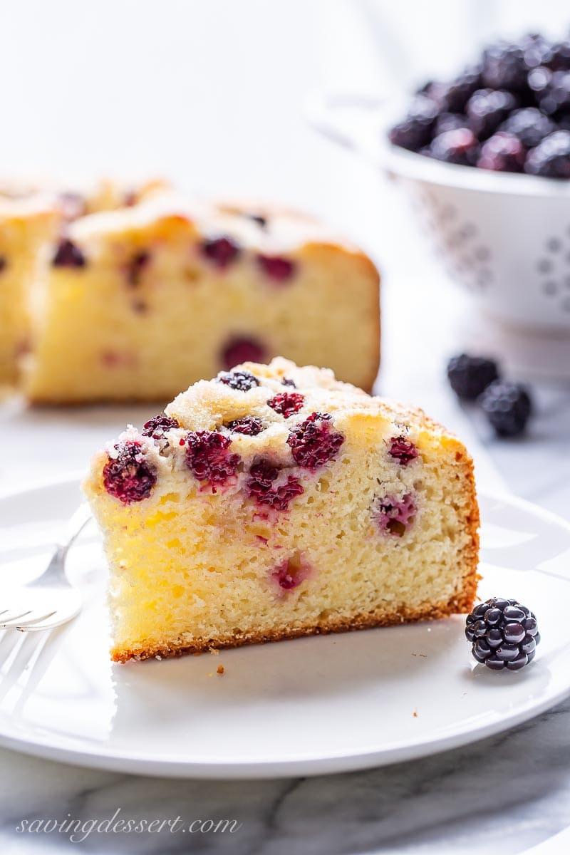 A slice of blackberry breakfast cake on a plate with fresh blackberries