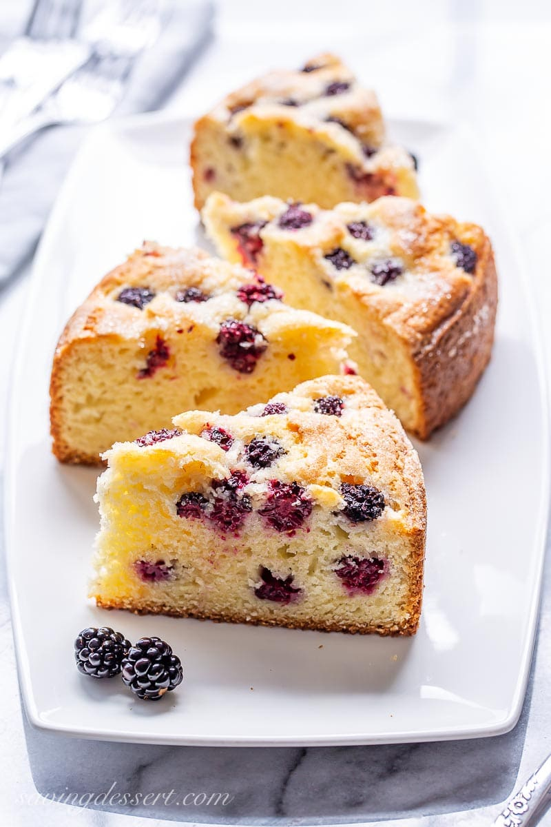 A platter with four slices of cake baked with fresh blackberries on top