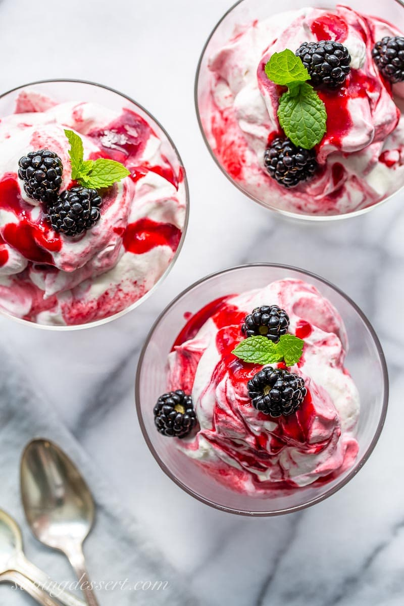 An overhead view of three clear glass dessert bowls filled with a blackberry fool mixture