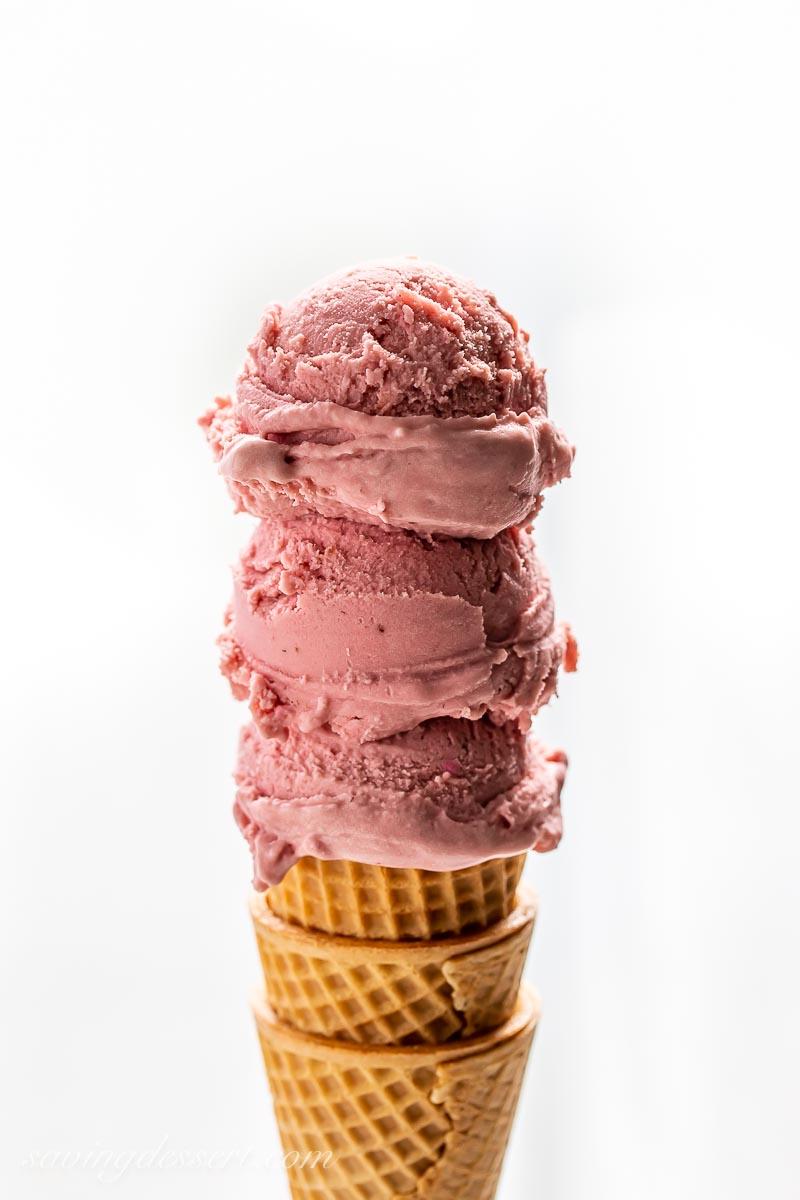 Three scoops of dark pinkish purple ice cream on a cone