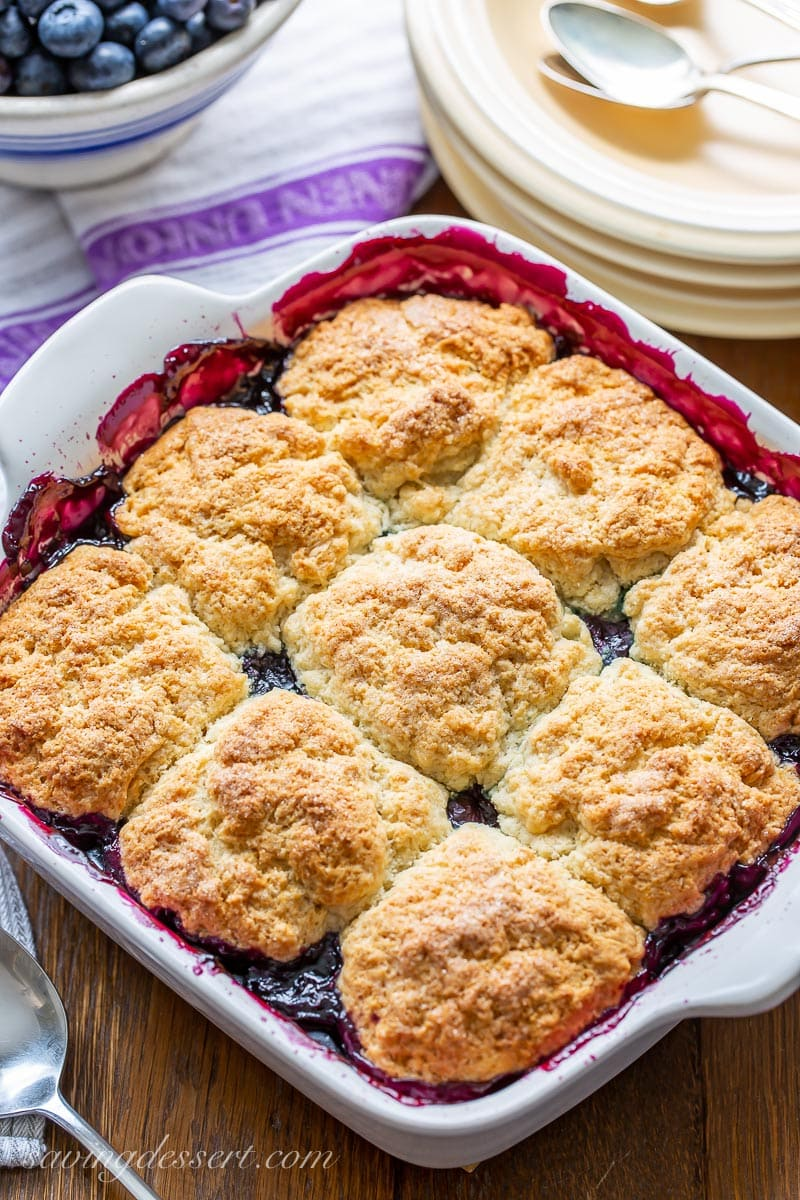 A casserole dish with biscuits floating in a pool of blueberry filling