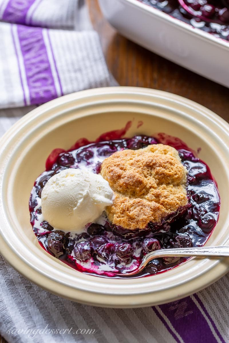 A bowl of blueberry cobbler and a scoop of vanilla ice cream with a spoon