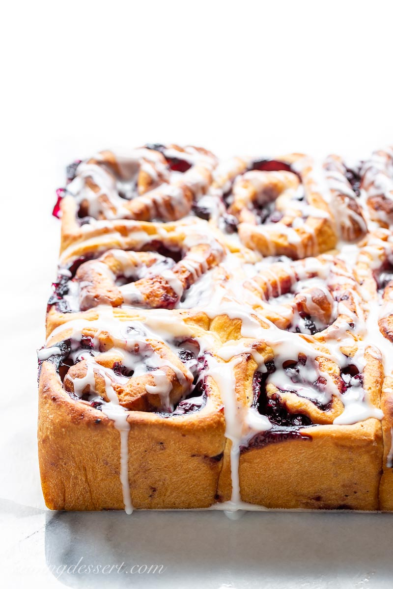 Golden brown sweet rolls with a blueberry filling, drizzled with icing