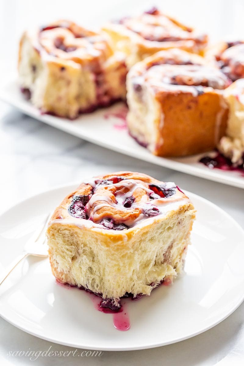 A plate with a flaky lemon blueberry sweet roll and a fork