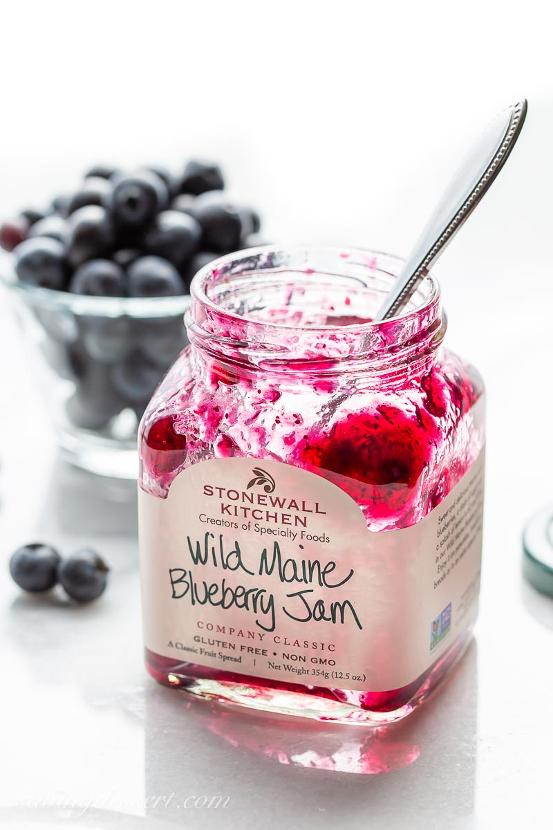 A jar of Wild Maine Blueberry Jam with a spoon and fresh blueberries