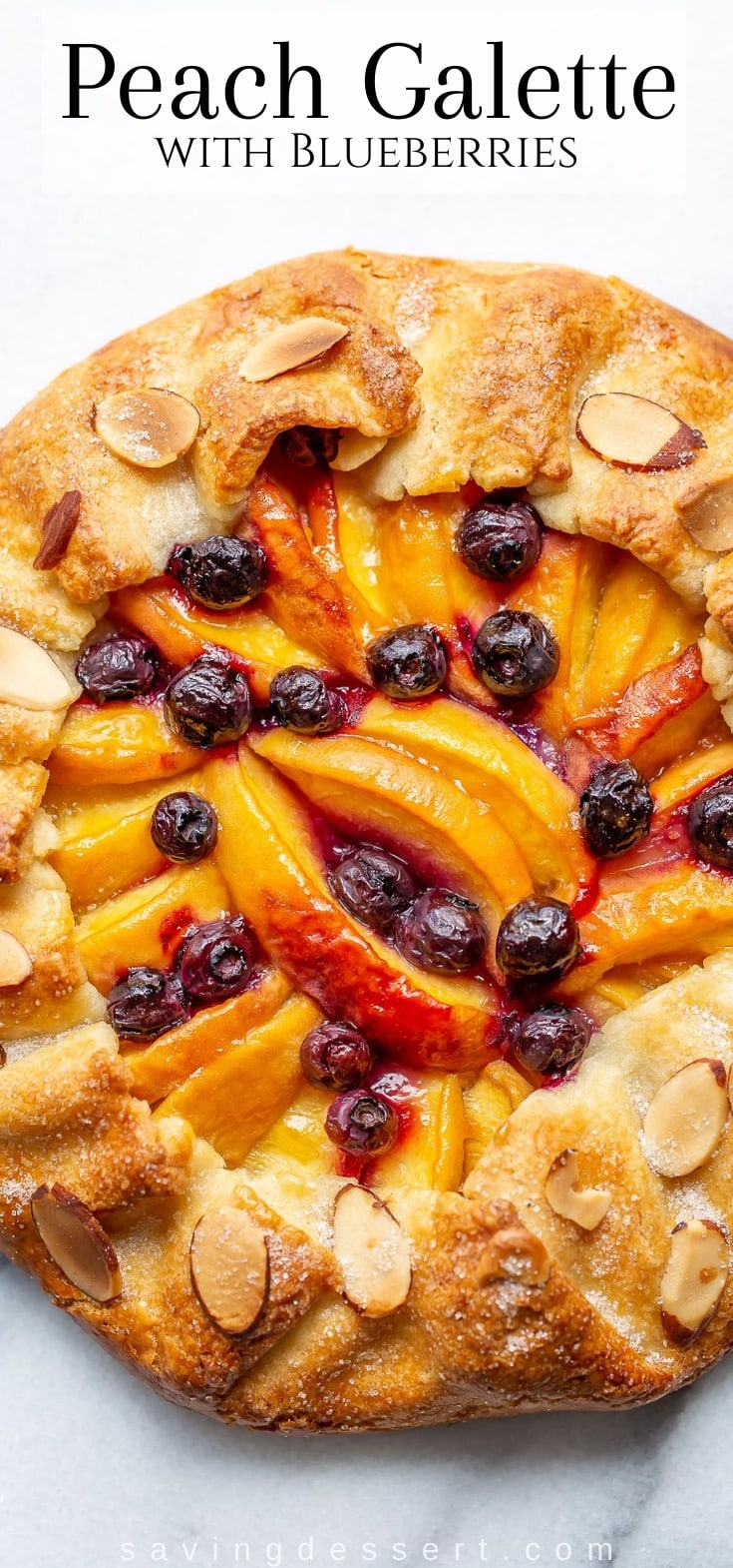 A close up shot of a peach galette with blueberries and sliced almonds