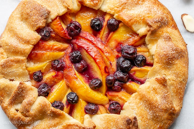 An overhead view of a peach galette with blueberries
