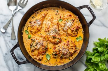 A skillet of sun-dried tomato chicken with basil and Parmesan