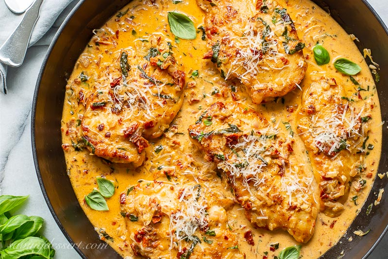 A closeup of a skillet with chicken breasts covered in a sun-dried tomato cream sauce with fresh basil and Parmesan