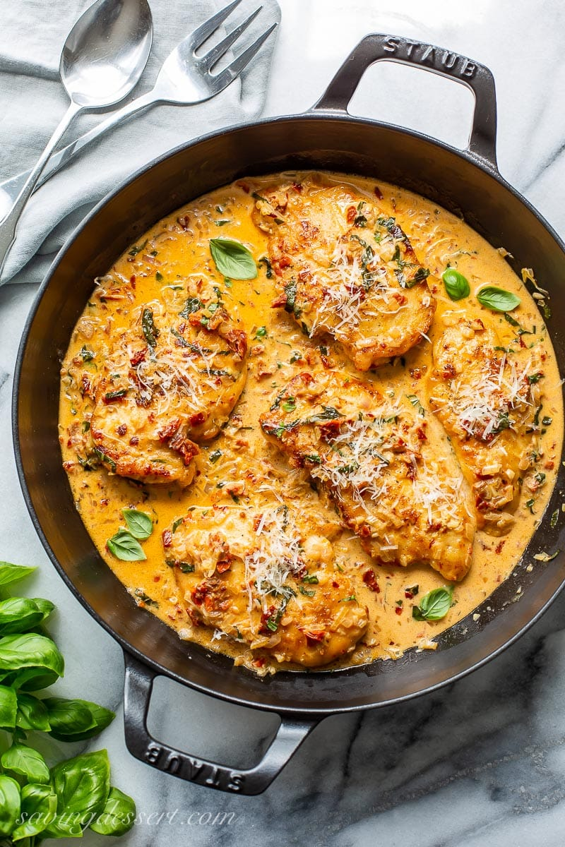 A skillet with chicken cutlets in a sun-dried tomato cream sauce
