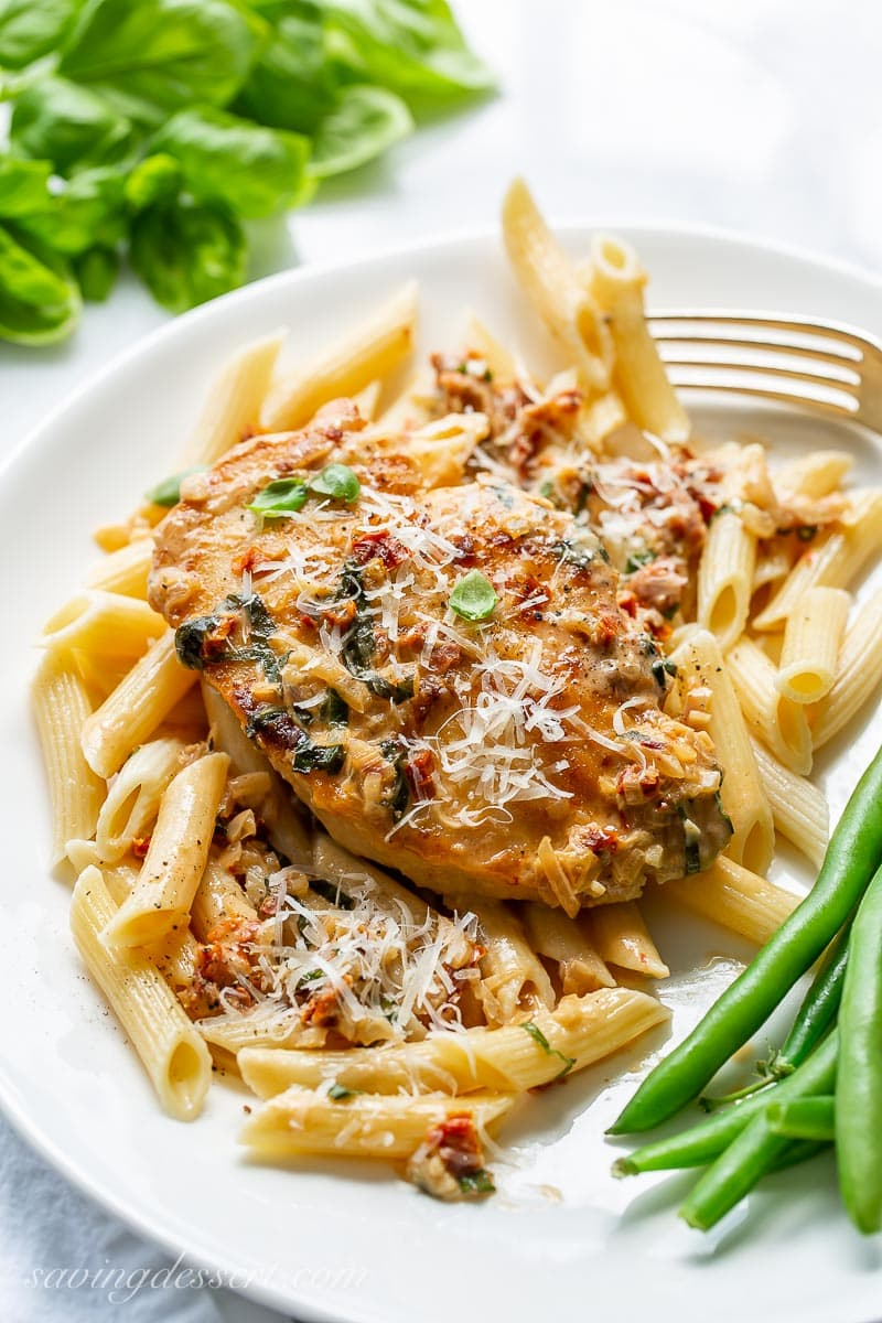 A plate with penne pasta and a chicken breast on top