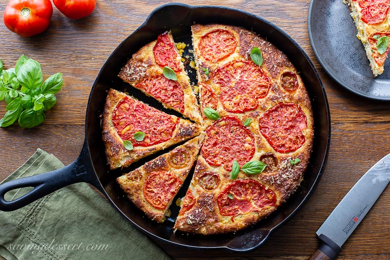 A cast iron skillet with sliced corn bread topped with tomatoes, cheese and basil leaves