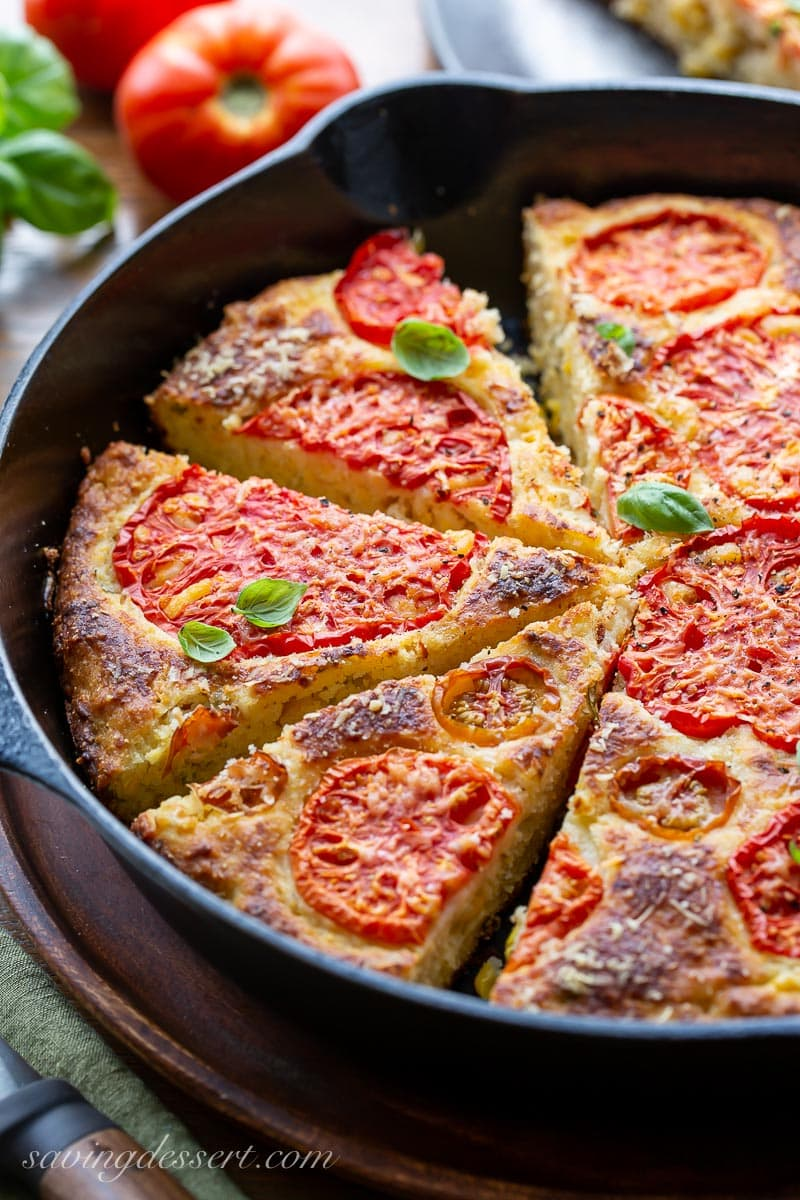 A side view of a cast iron skillet filled with sliced cornbread topped with tomatoes and fresh basil leaves