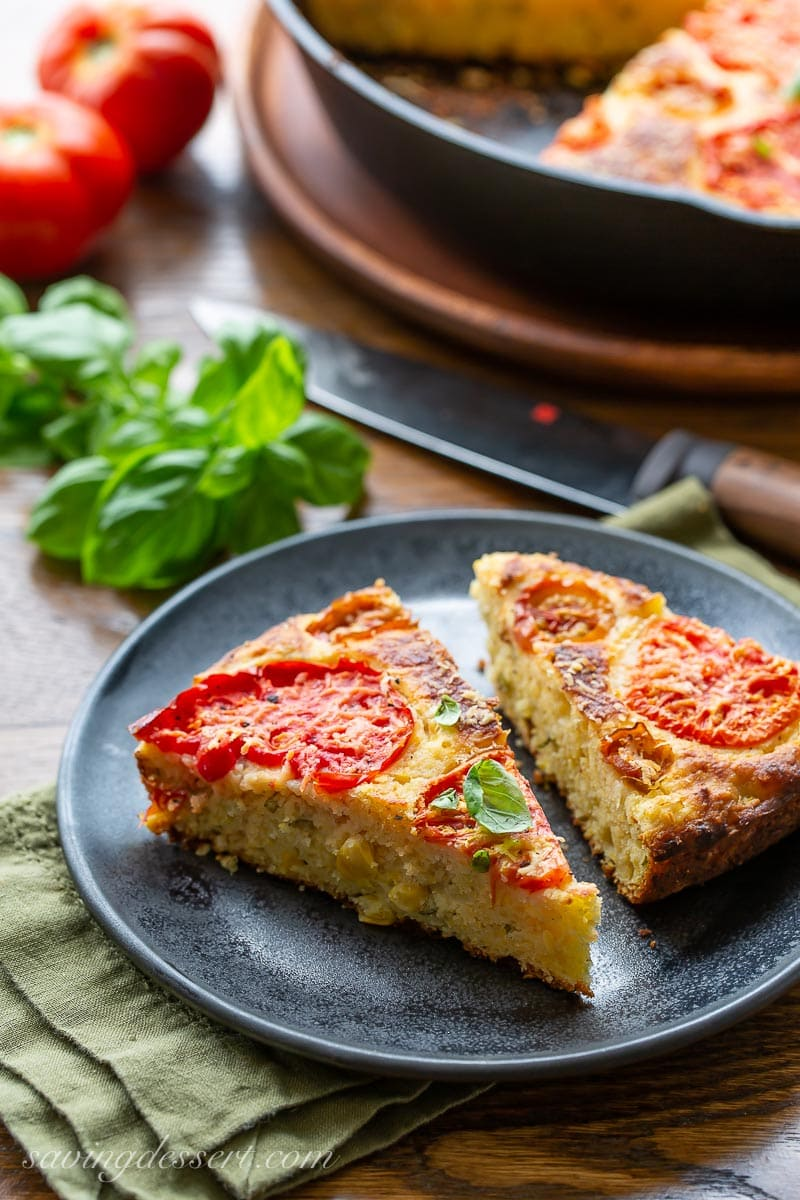 Two slices of tomato topped cornbread with fresh basil
