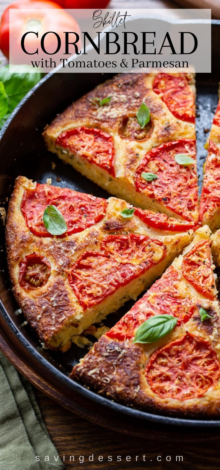 A cast iron skillet with cornbread topped with tomatoes and basil