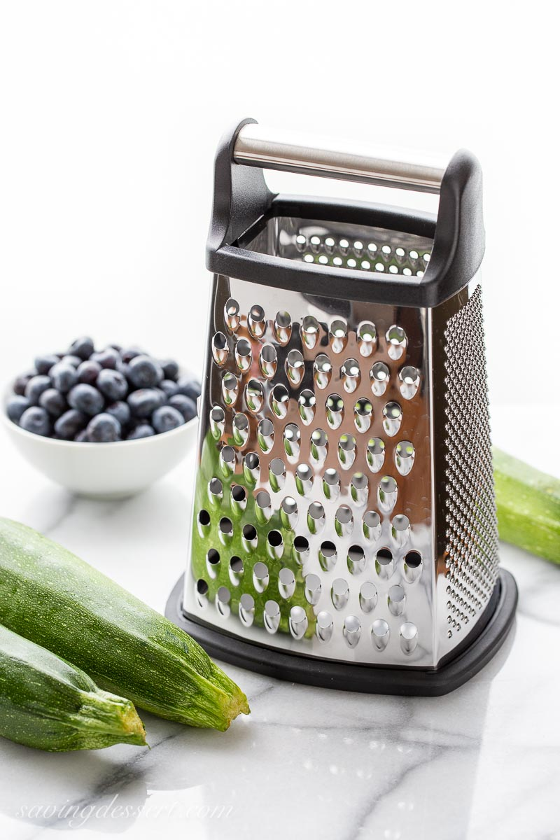 A large box grater with on a marble top