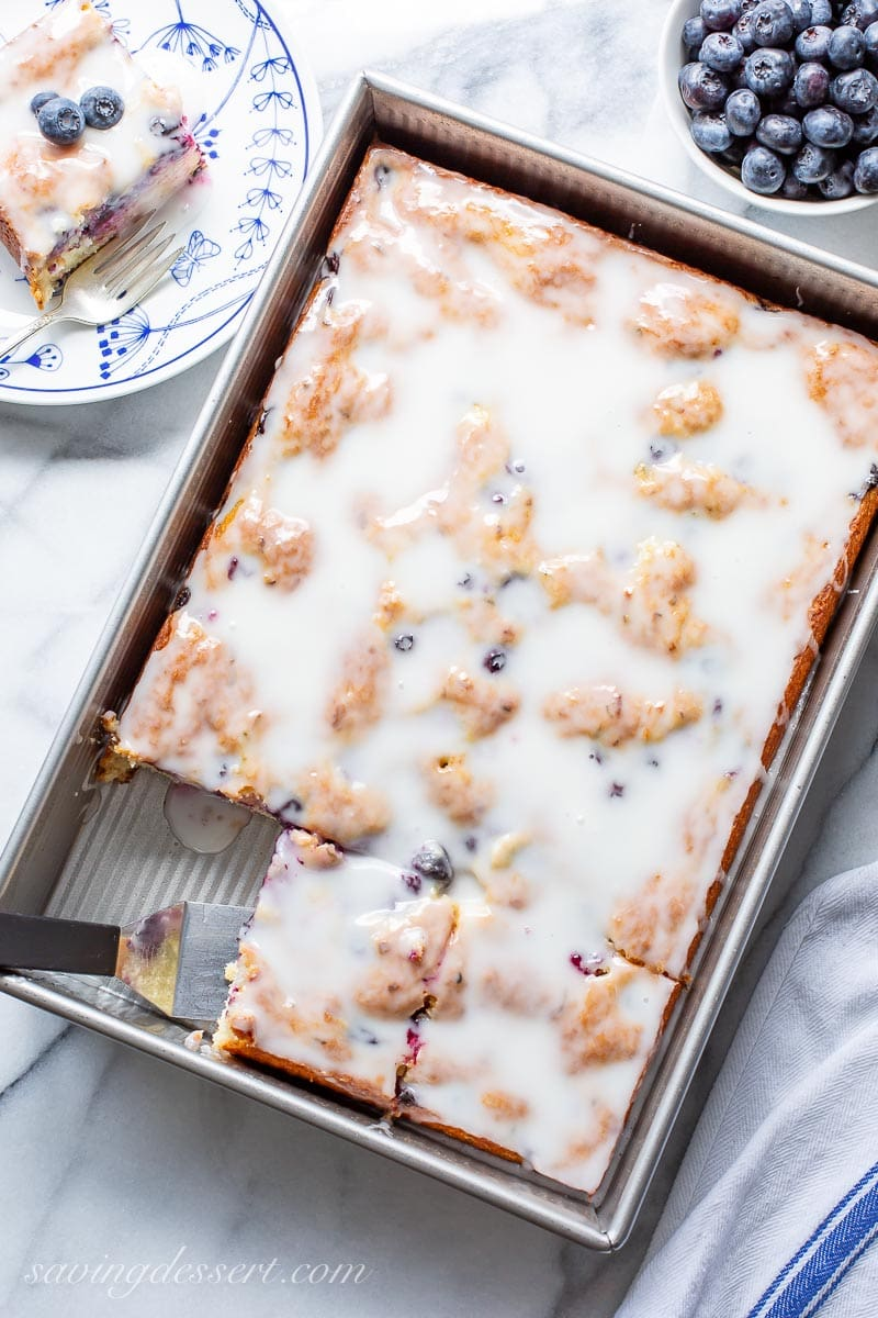 A pan with a sliced blueberry zucchini cake topped with a buttermilk glaze
