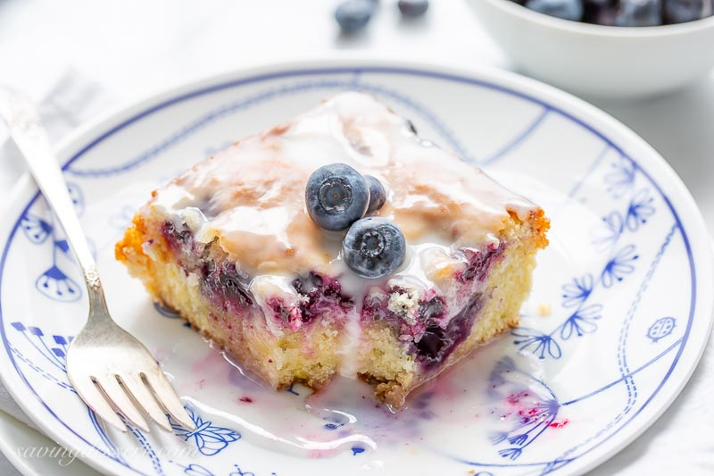 A slice of blueberry lemon zucchini cake on a plate topped with a few fresh blueberries and a lemon glaze
