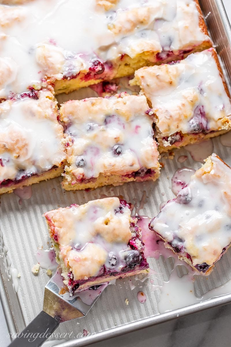 A pan with a sliced blueberry zucchini cake with a buttermilk glaze on top