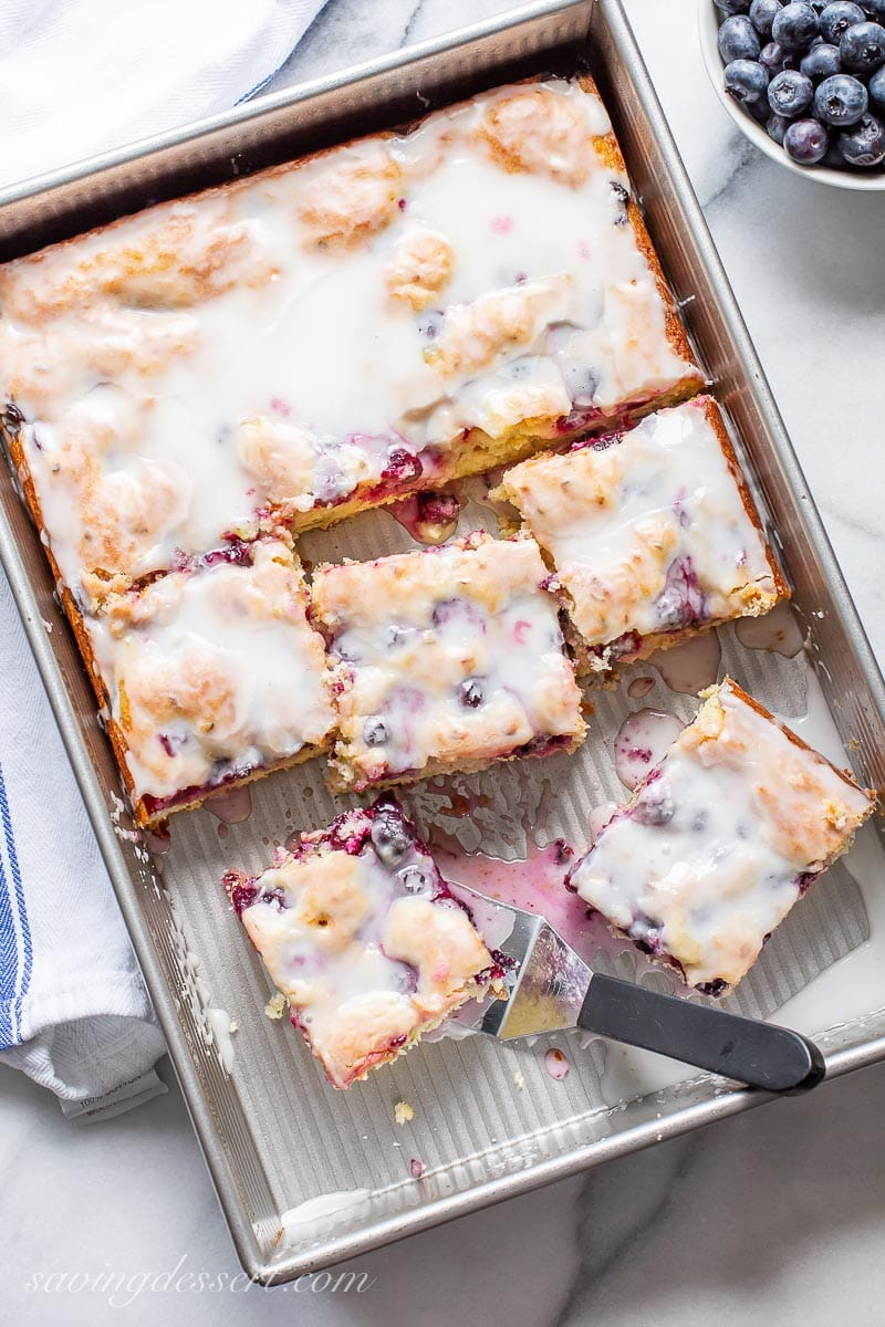A pan with sliced blueberry cake and a spatula with a buttermilk glaze on top
