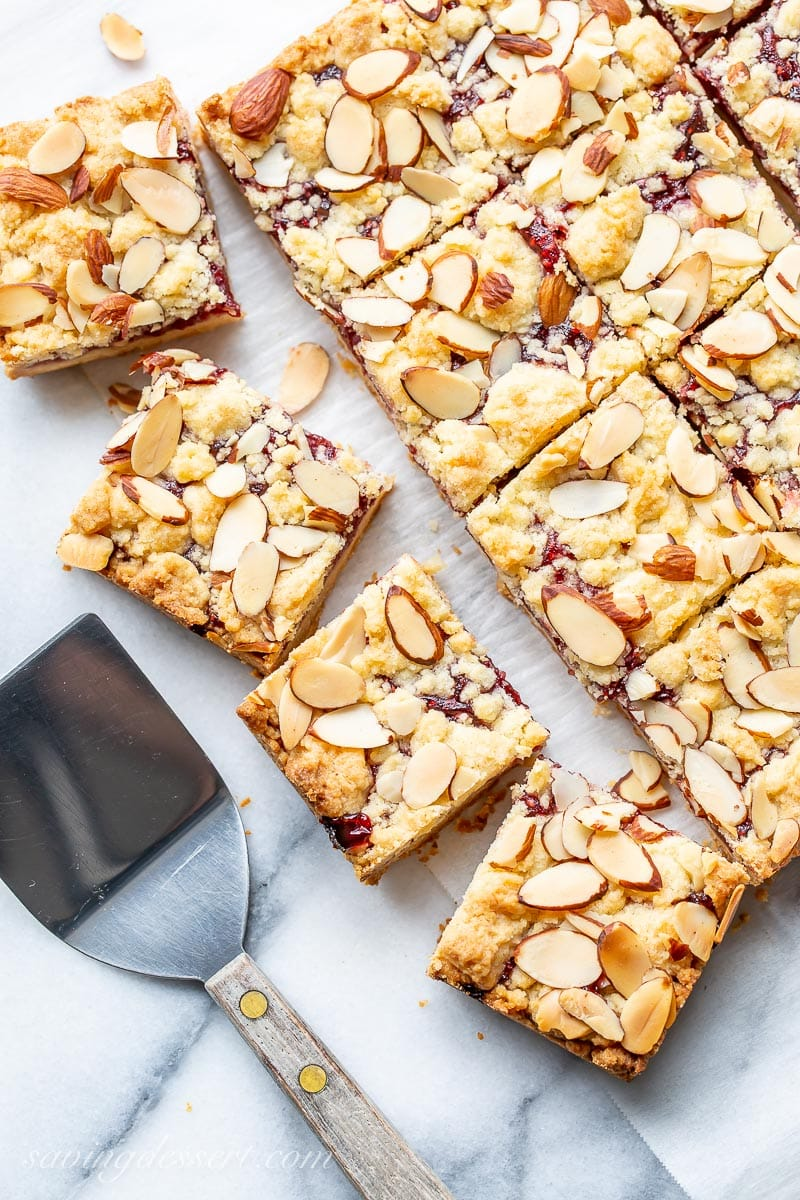 Raspberry Almond Squares on marble with a spatula