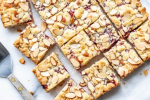 An overhead view of sliced raspberry almond bars and a spatula