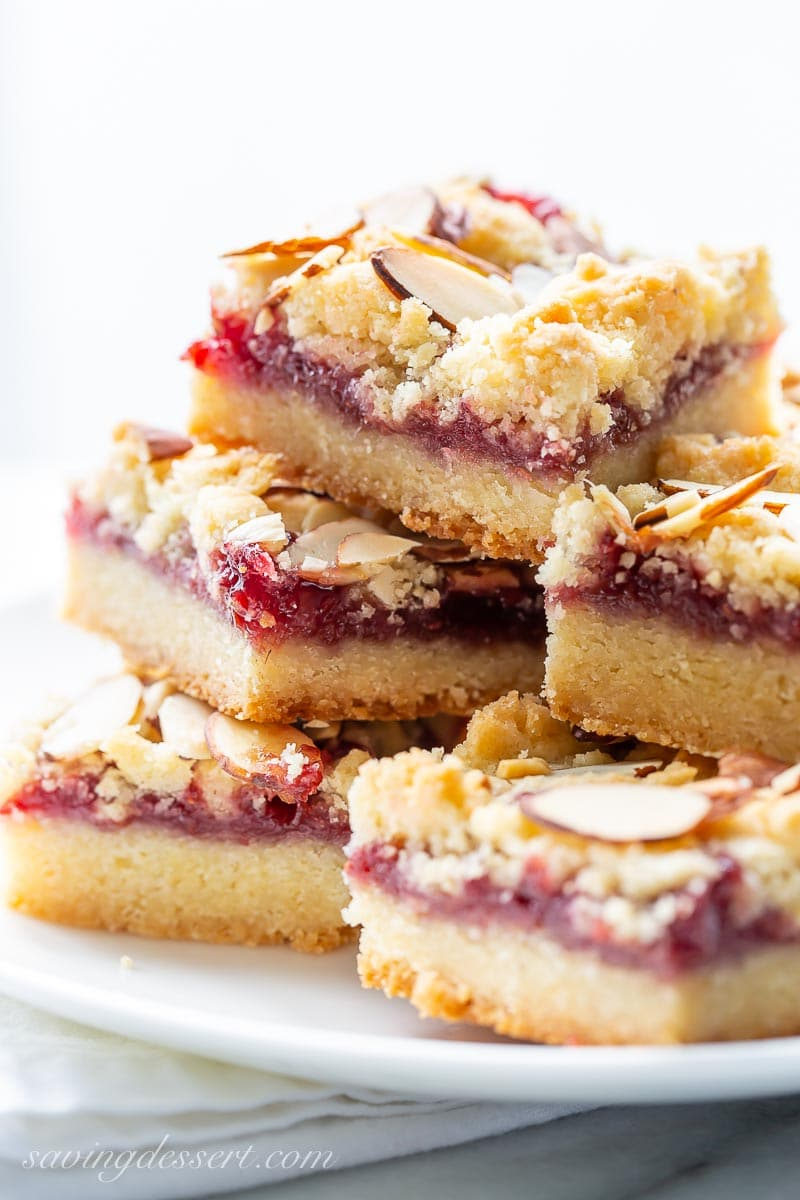 A side view of a stack of raspberry almond bars on a plate