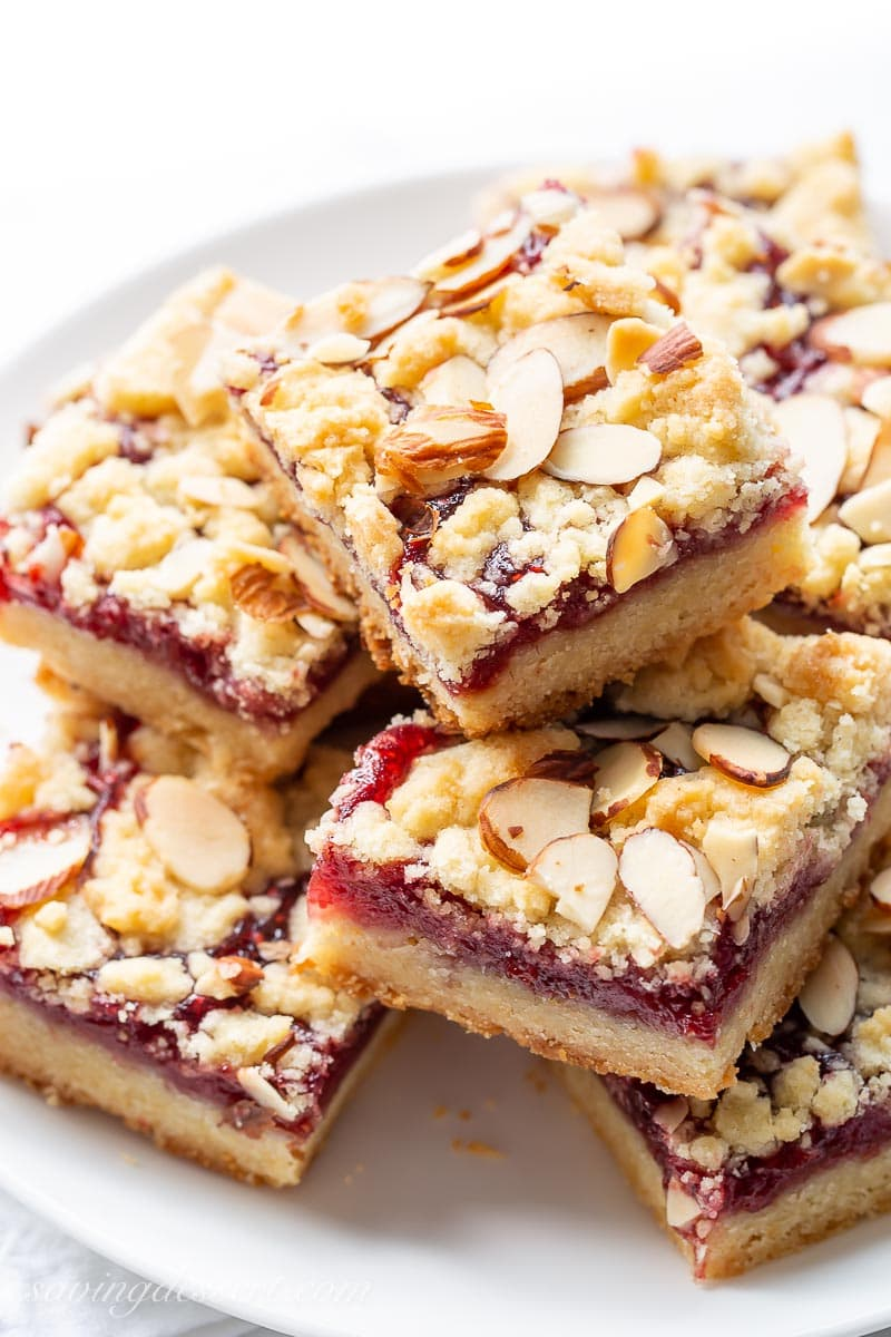 A plate stacked with raspberry bars topped with sliced almonds