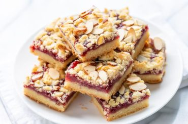 A plate of raspberry bars topped with sliced almonds