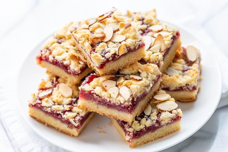 A plate of jam crumble bars topped with sliced almonds