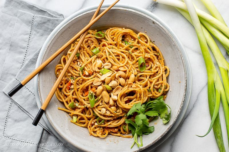 A bowl of spicy peanut noodles with chopsticks