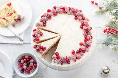 An overhead view of a sliced Cranberry Christmas Cake decorated with sugared cranberries