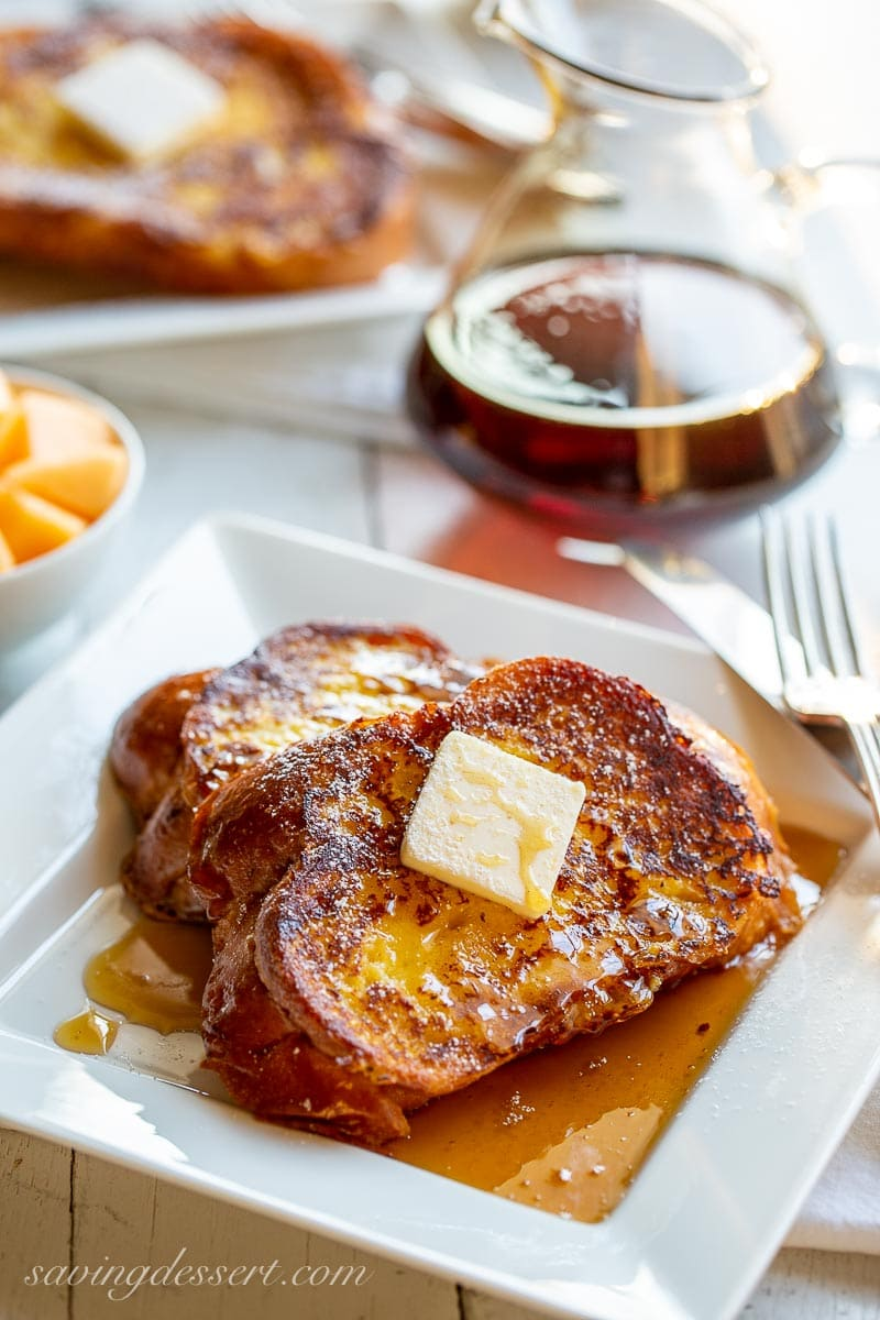 A table with two plates of French toast, and a carafe of syrup