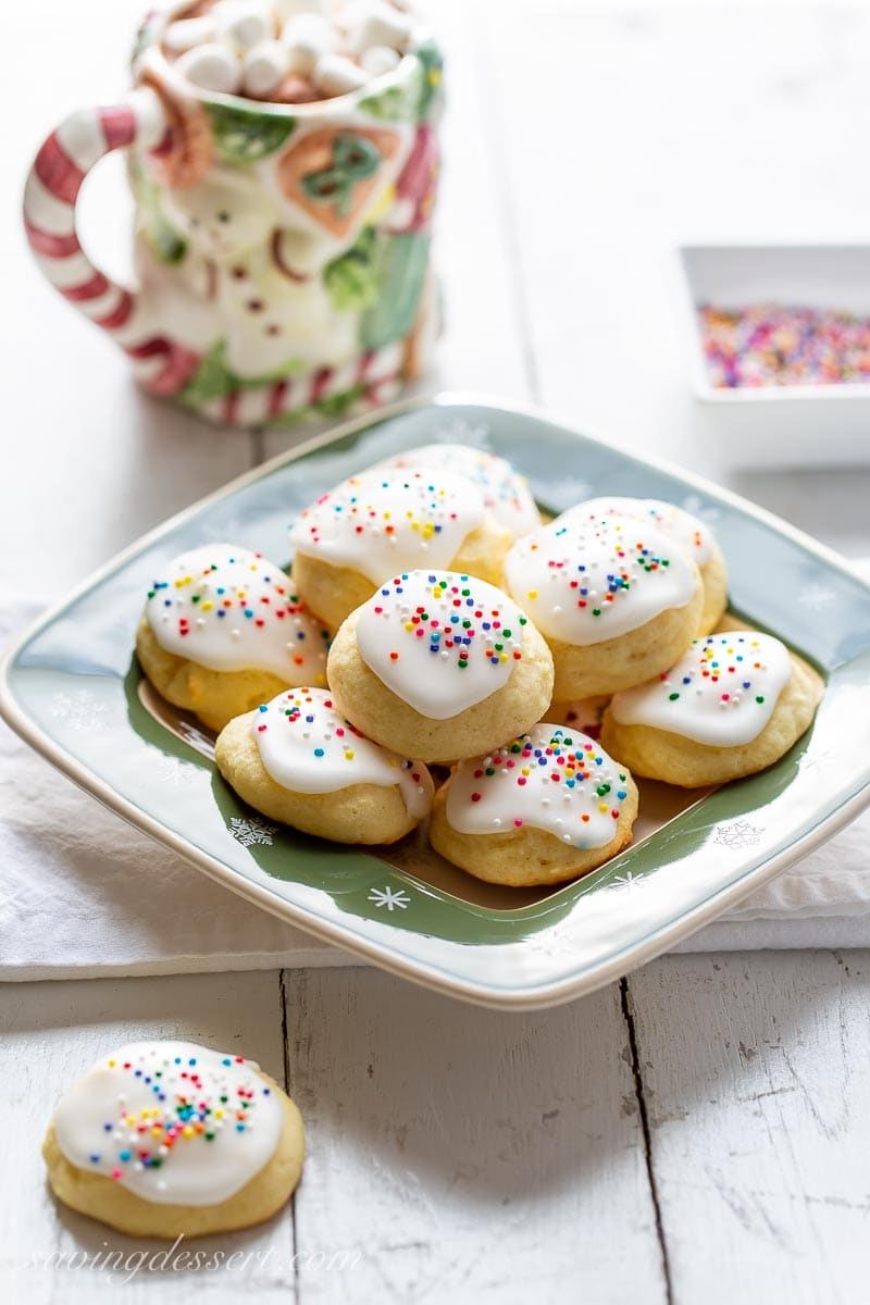 A plate of soft cake-like cookies with a lemon glaze and sprinkles
