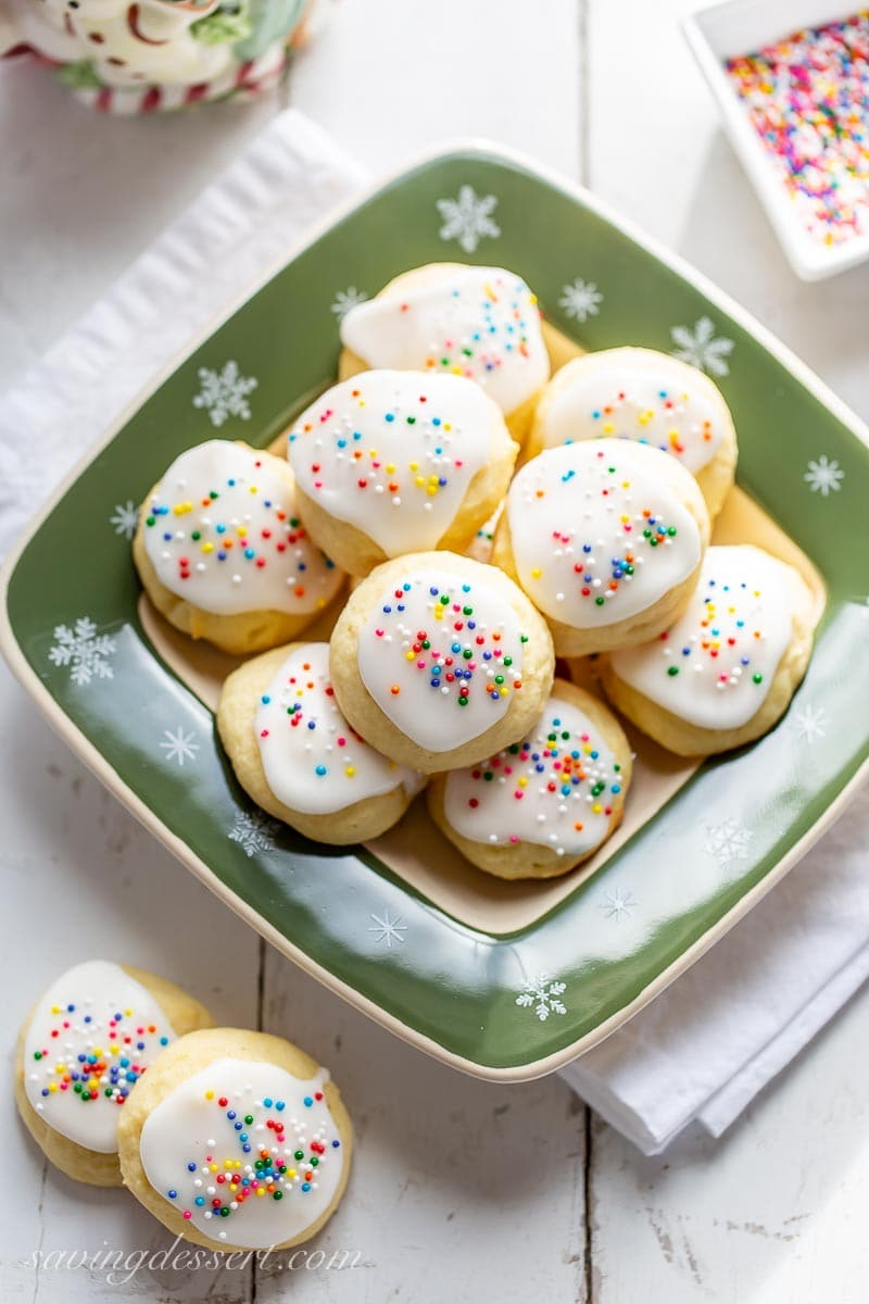 An overhead view of a holiday plate of soft vanilla and lemon cookies with a lemon icing and sprinkles