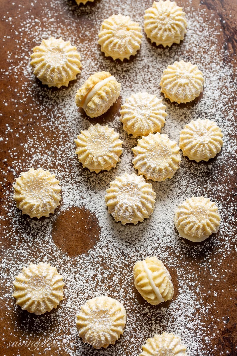 A cookie sheet with little lemon cookies dusted with powdered sugar