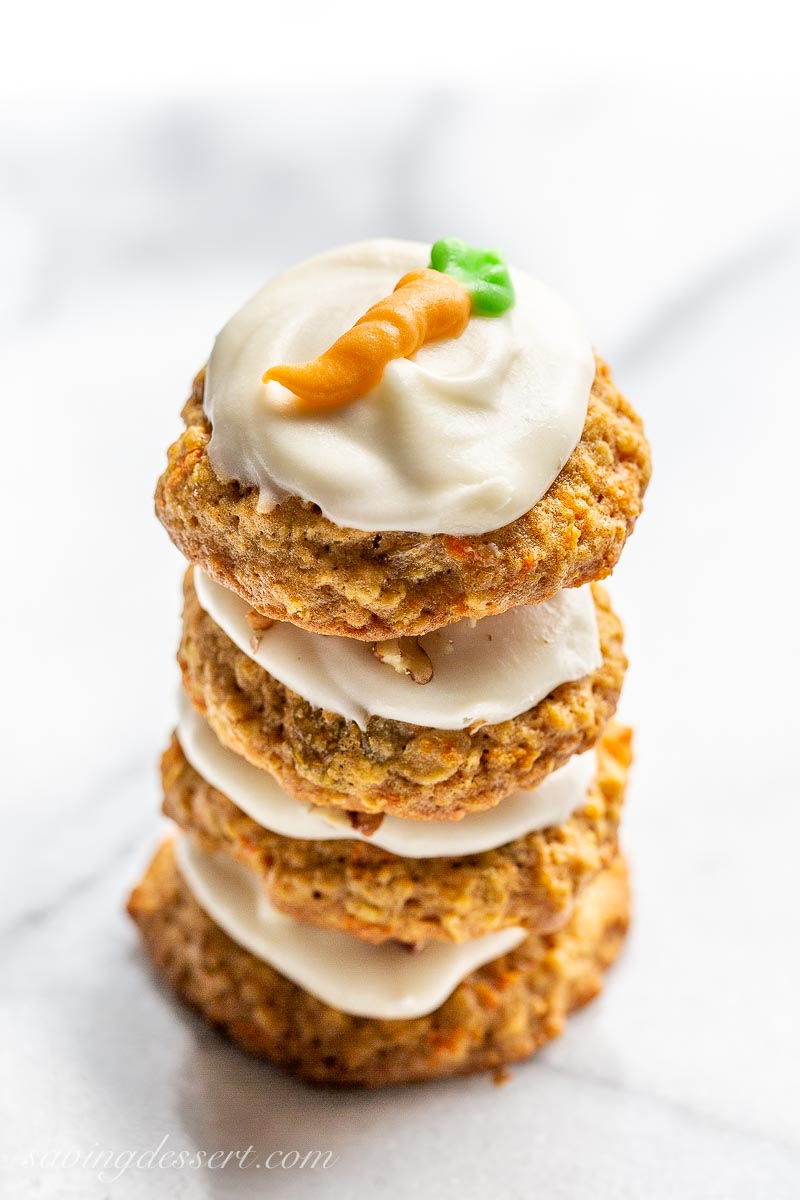 Carrot cake cookies with icing in a stack and decorated with a piped carrot