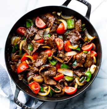 A skillet with steak, tomatoes and green peppers