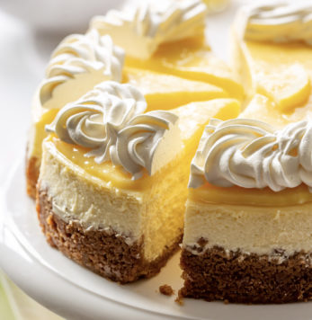 A sliced lemon cheesecake topped with lemon curd and whipped cream
