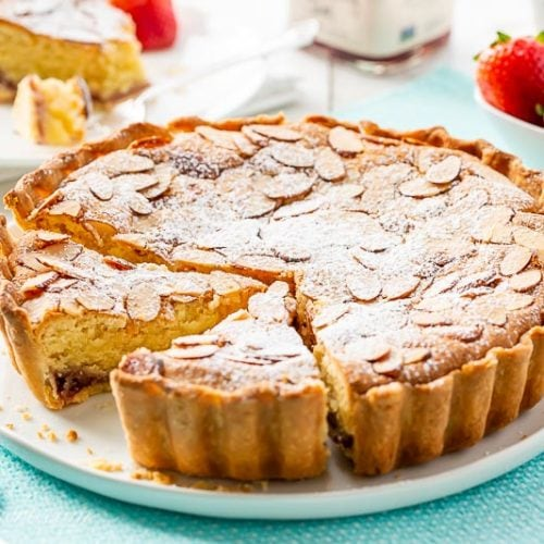 Sliced Bakewell Tart on a platter served with strawberries