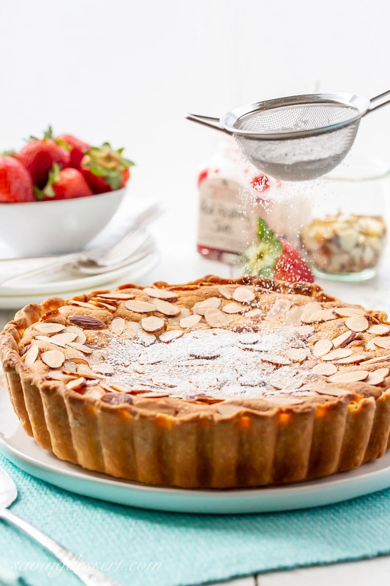 An almond topped tart being dusted with powdered sugar