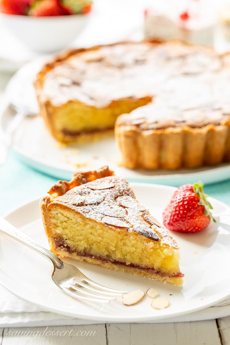 A slice of an almond topped Bakewell Tart on a plate with a strawberry
