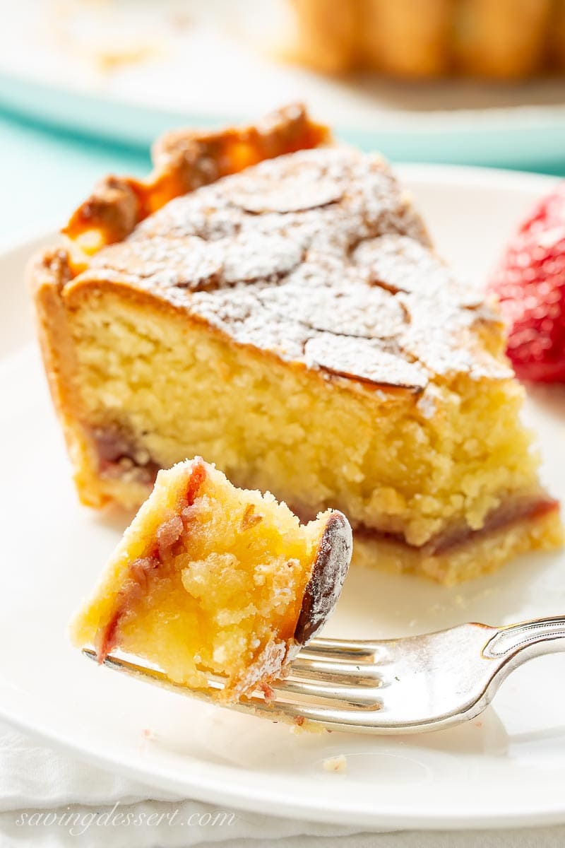 A closeup of a slice of almond tart with a bite on a fork